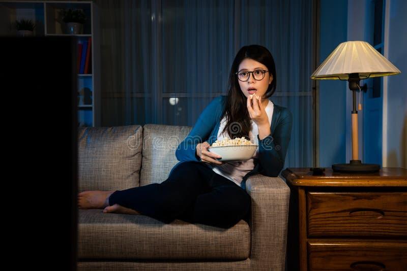 拿着玉米花箱子和看电视的可爱的女孩 免版税图库摄影