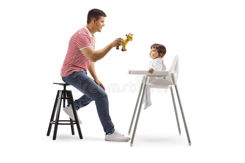 拿着玩具和给椅子的父亲一个婴孩赋予生命 图库摄影