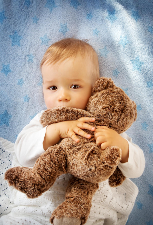 拿着玩具熊的一个岁婴孩 库存照片