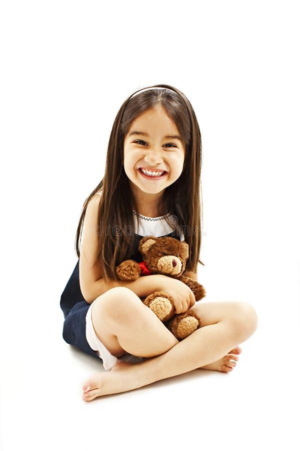 拿着玩具熊的小女孩,坐地板 免版税库存图片