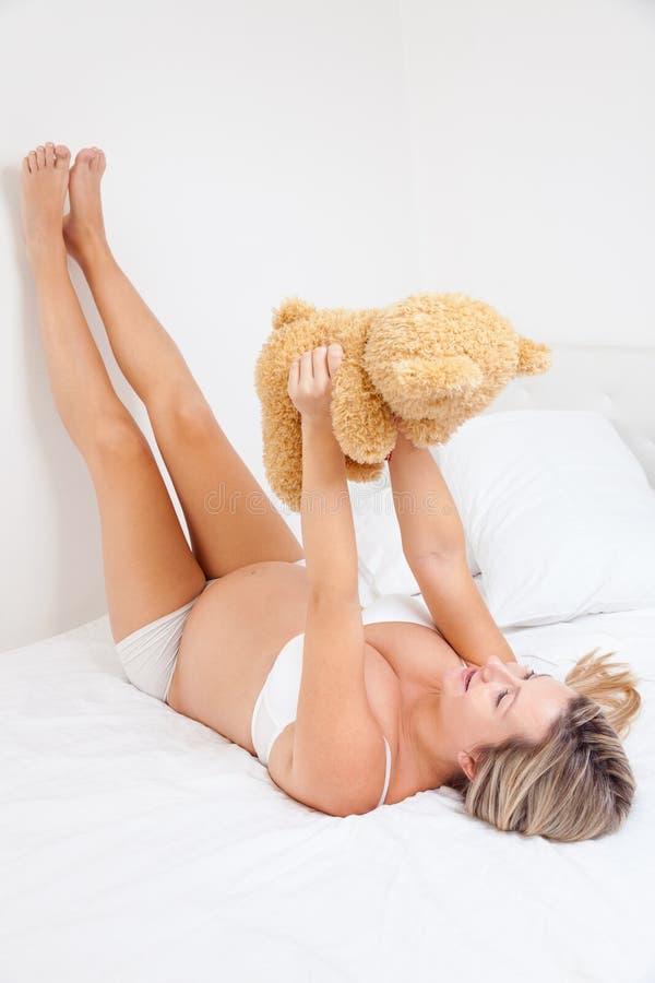 拿着玩具熊的愉快的孕妇 图库摄影