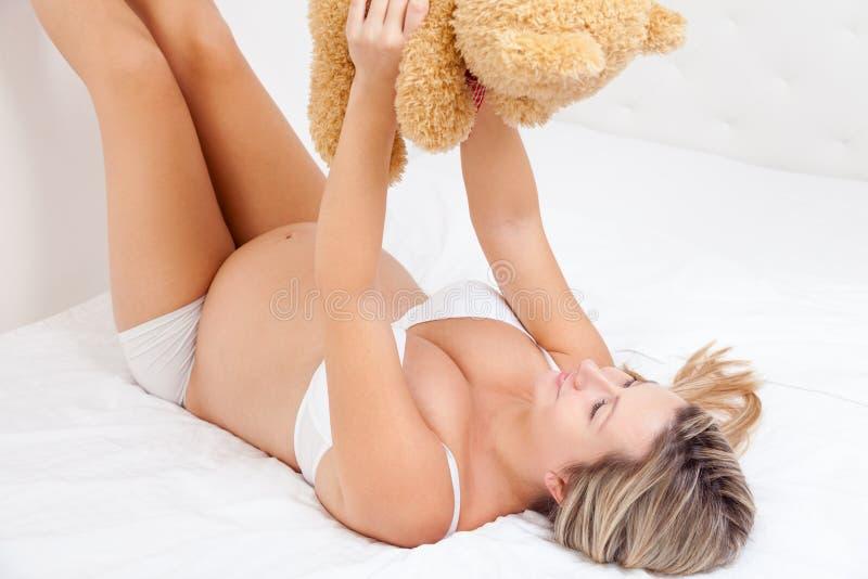 拿着玩具熊的愉快的孕妇 免版税库存图片