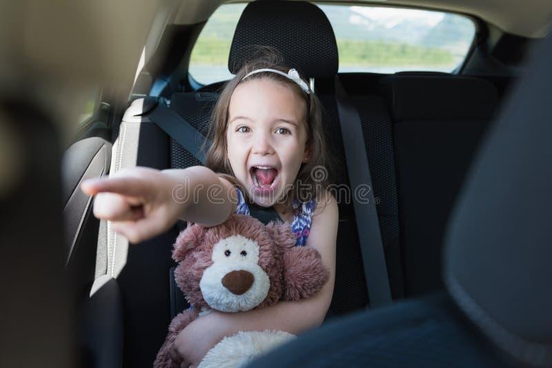 拿着玩具熊的激动的女孩,当打手势在汽车时 库存图片