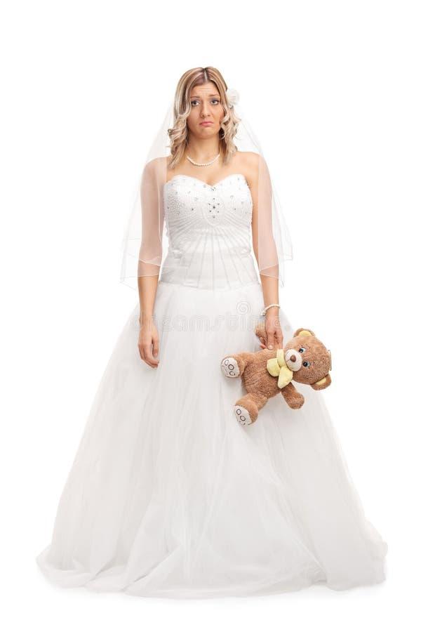 拿着玩具熊的年轻哀伤的新娘 免版税库存图片