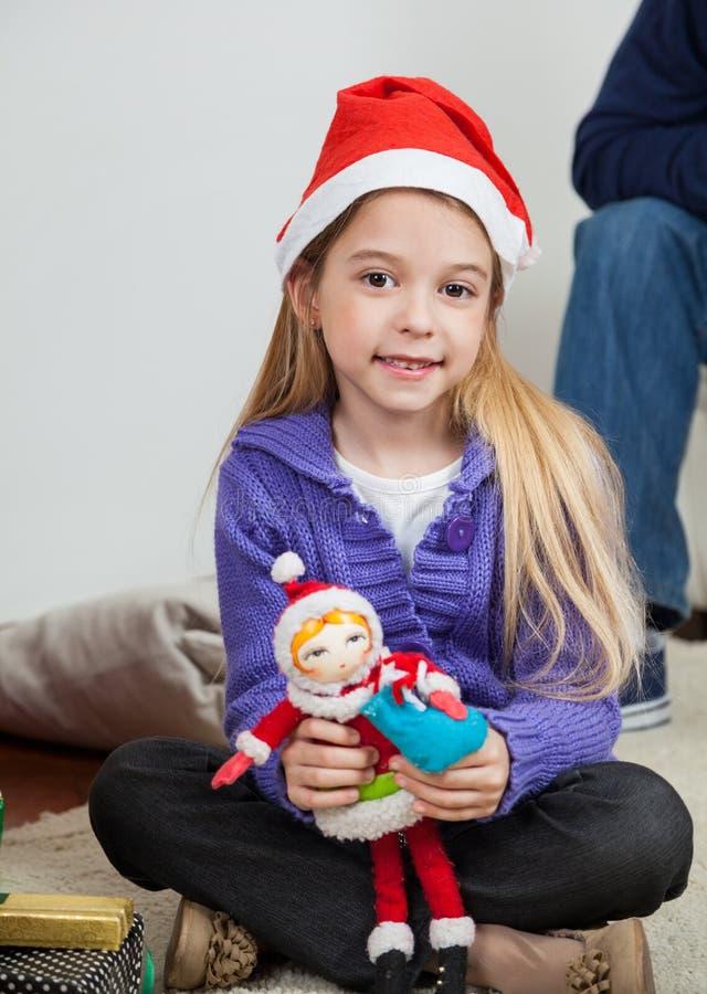 拿着玩具的圣诞老人帽子的女孩 免版税库存照片