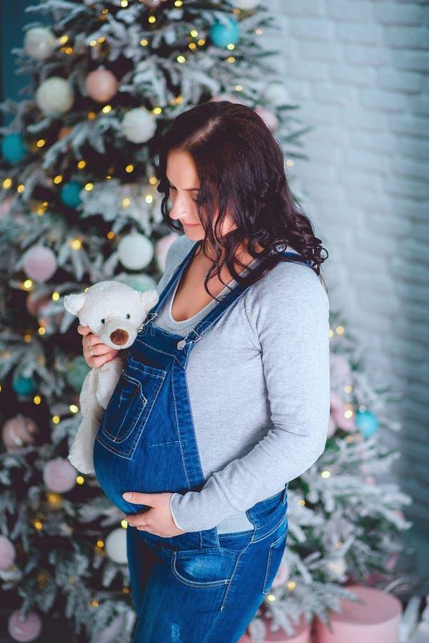 拿着玩具的蓝色牛仔布总体的美丽的年轻怀孕的女孩 免版税库存照片