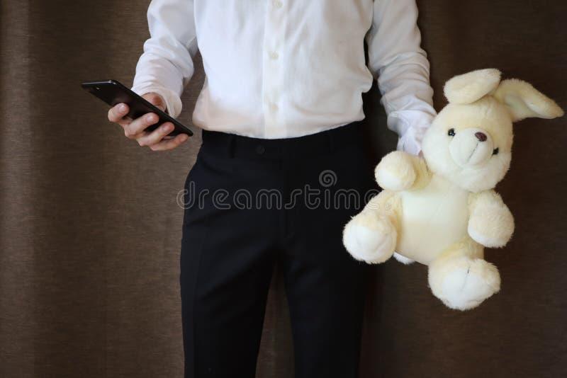 拿着玩具野兔和电话的白色衬衫和黑色裤子的年轻人 一个人用一只大玩具兔子 爱的一个人 Th的一件礼物 免版税库存图片