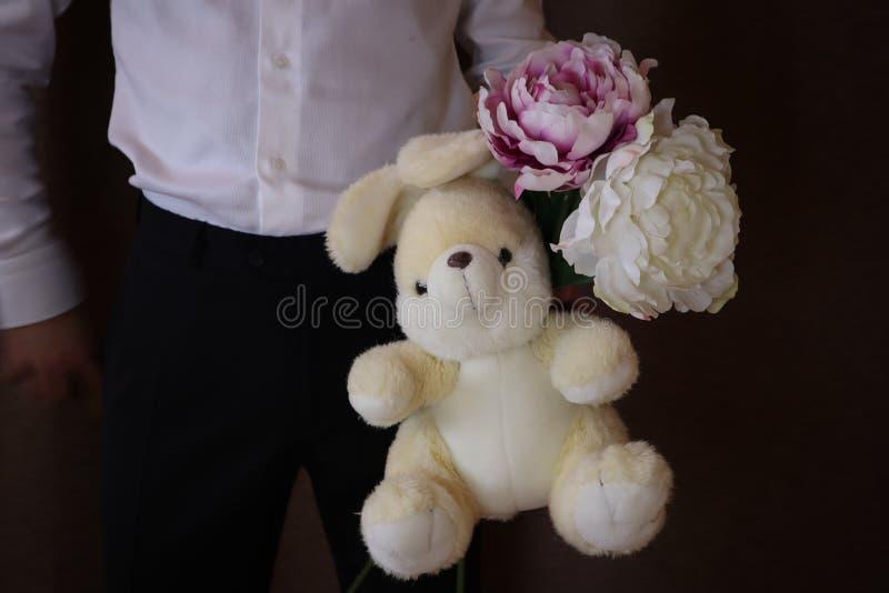 拿着玩具野兔和花的白色衬衫和黑色裤子的年轻人 有牡丹和一只大玩具兔子的一个人 爱的一个人 图库摄影