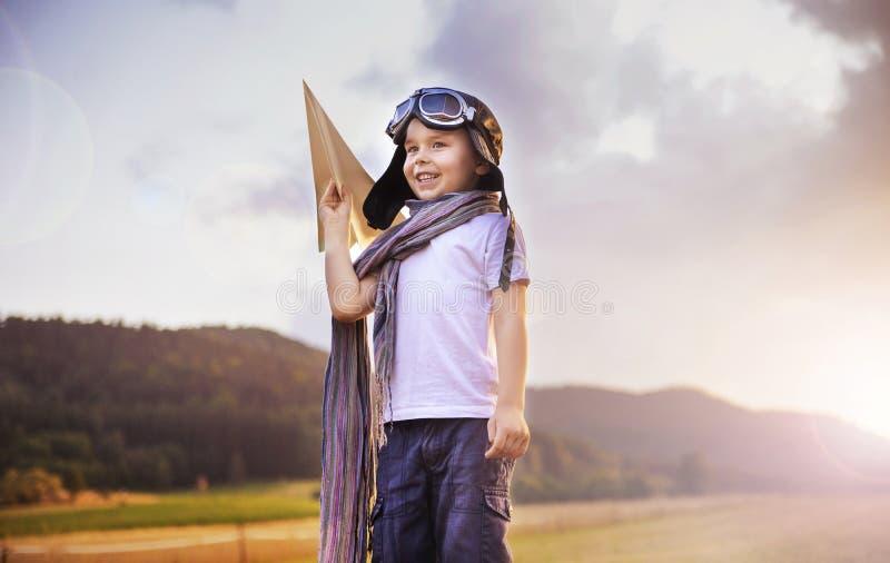 拿着玩具飞机的逗人喜爱的矮小的飞行员 图库摄影