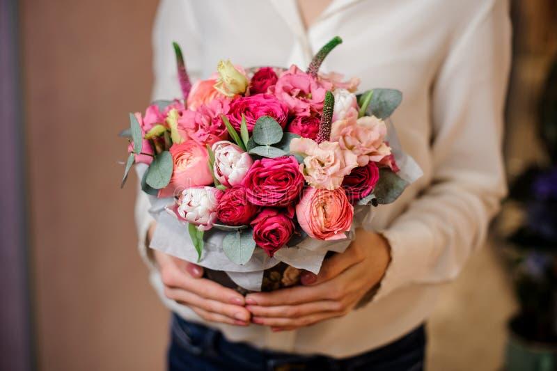 拿着玫瑰的美丽的花束与绿色叶子的女孩