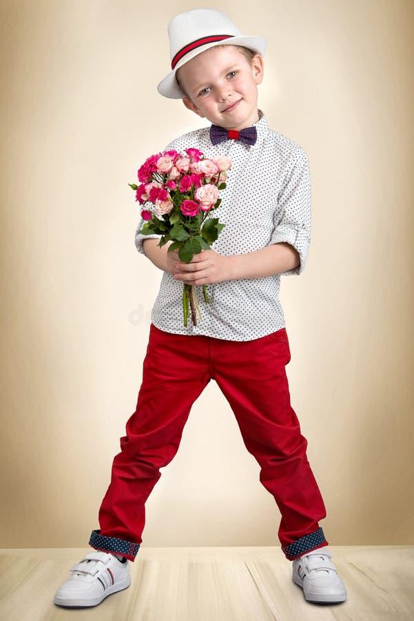 拿着玫瑰的花束帽子的时髦的男孩 儿童` s时尚 库存图片