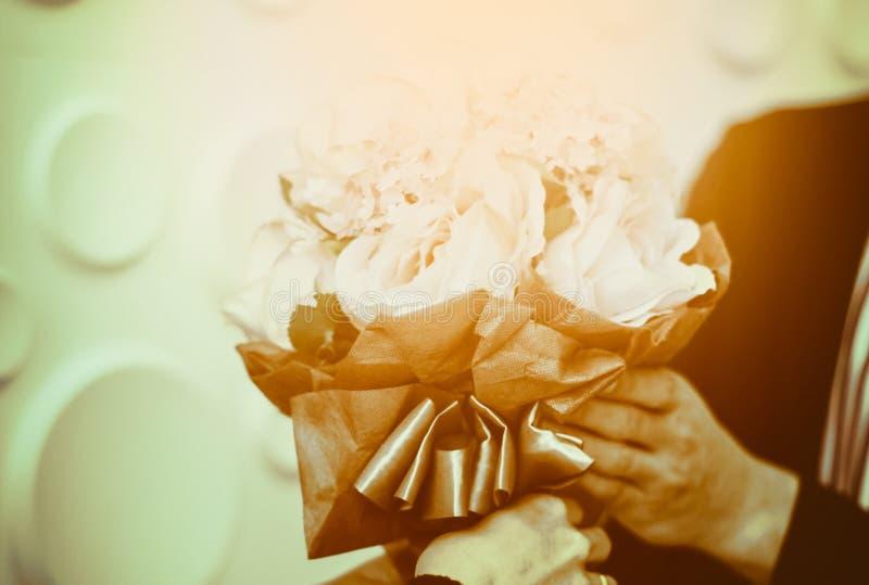 拿着玫瑰花束的花束青年人手中为一个女孩恋人,温暖的颜色,葡萄酒样式,浪漫概念关心 图库摄影