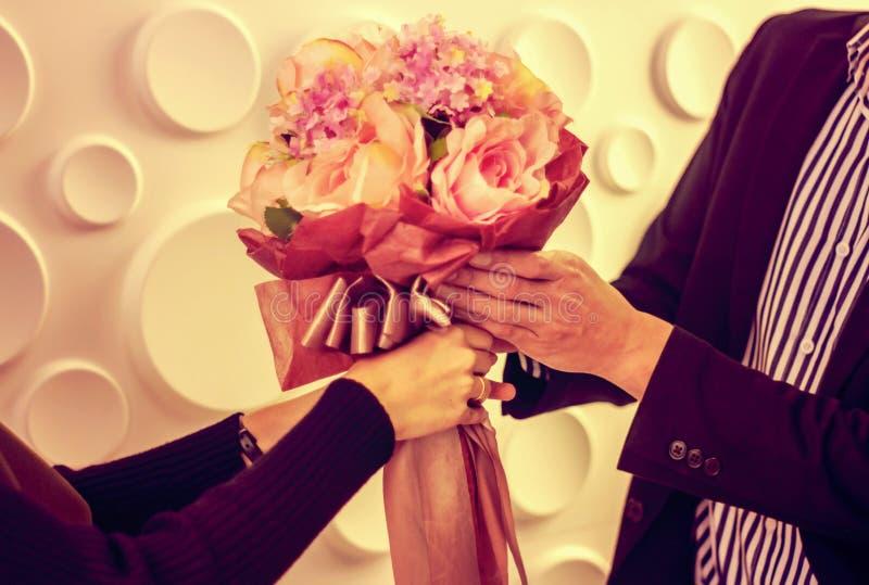 拿着玫瑰花束的花束青年人手中为一个女孩恋人,温暖的颜色,葡萄酒样式 库存照片