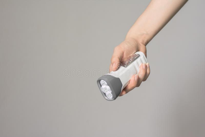 拿着现代手电,LED手电的接近的妇女手 免版税图库摄影