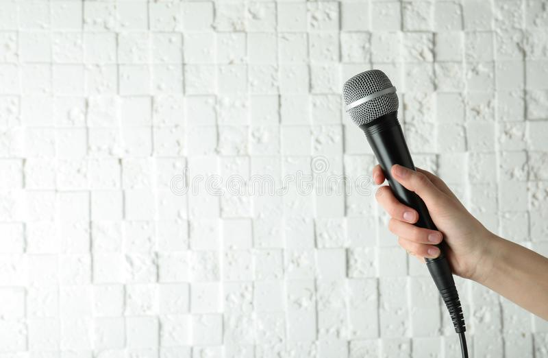 拿着现代话筒的妇女在白色墙壁,特写镜头附近 免版税图库摄影