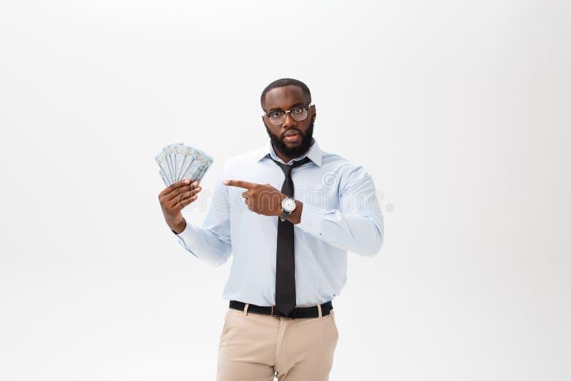 拿着现金和严肃的看的照相机的非裔美国人的商人 室内,隔绝在灰色背景 免版税库存照片