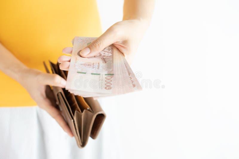 拿着现金和开放棕色皮革钱包的手的关闭 拉扯泰国金钱Bahtand右手藏品钱包的左手 免版税库存照片