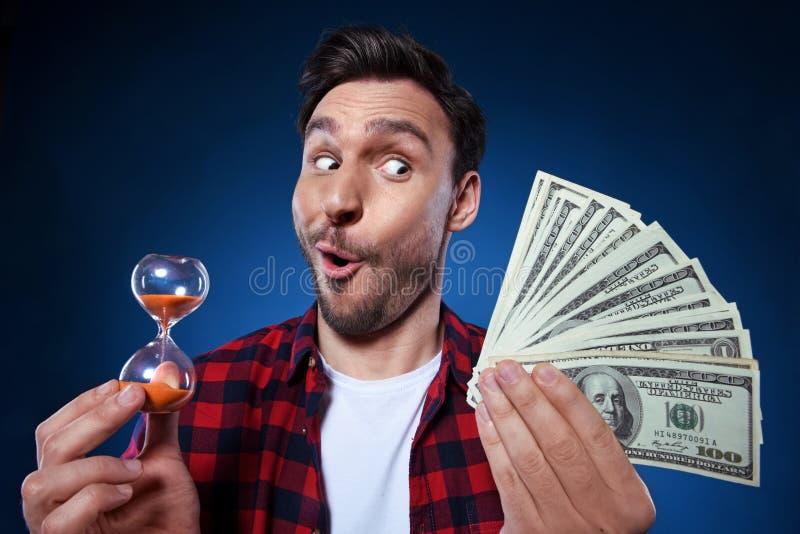 拿着现金和滴漏的滑稽的人 图库摄影