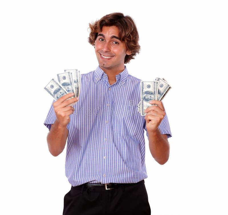 拿着现金美元的微笑的年轻人 免版税库存图片