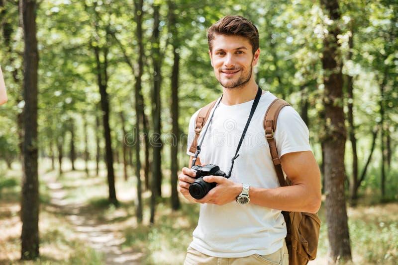 拿着现代照片照相机的愉快的年轻人摄影师户外 免版税图库摄影