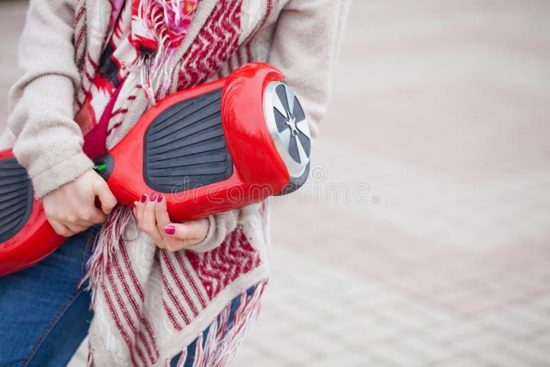 拿着现代红色电微型segway或翱翔委员会滑行车的女孩 免版税库存图片