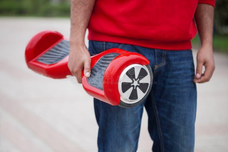 拿着现代红色电微型segway或翱翔委员会滑行车的男孩 库存照片