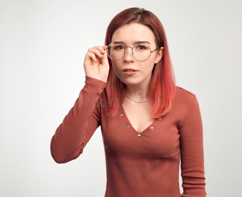 拿着玻璃和斜眼看设法的美丽的年轻女人读在他前面的题字 免版税库存照片