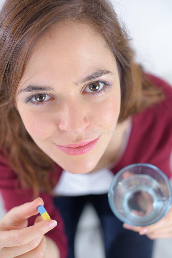 拿着玻璃水和采取药片的俏丽的妇女 免版税库存照片