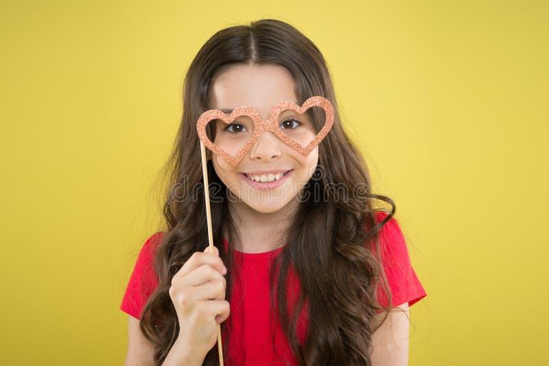 拿着玻璃照片在棍子的滑稽的小女孩摊支柱 与花梢党支柱的逗人喜爱的孩子 党装饰供应商 库存图片