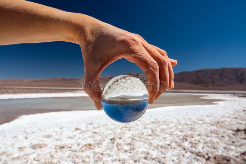拿着玻璃球的手在盐湖在阿塔卡马高原 免版税库存照片