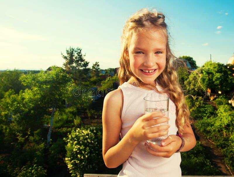 拿着玻璃用水的女孩 免版税图库摄影