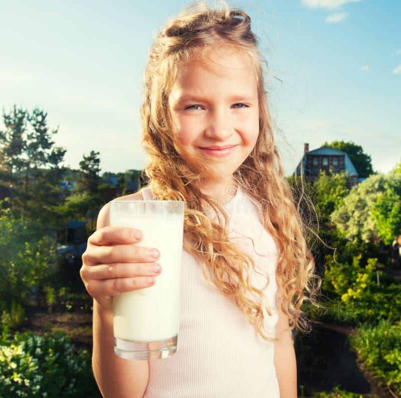 拿着玻璃用牛奶的女孩 库存照片