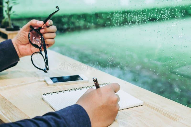 拿着玻璃的手,写在纸笔记购物清单在咖啡馆用仙人掌 免版税库存照片