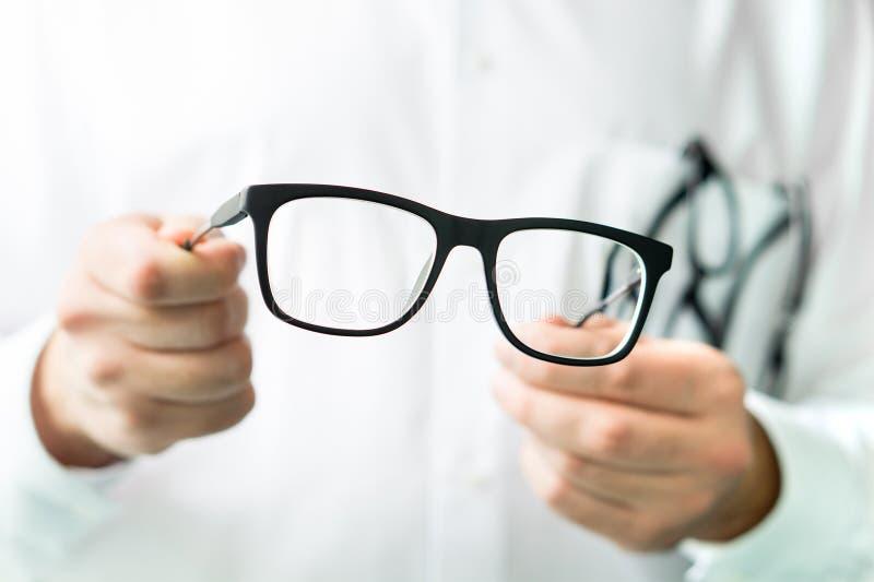 拿着玻璃的眼镜师 显示新的透镜的眼科医生 库存图片