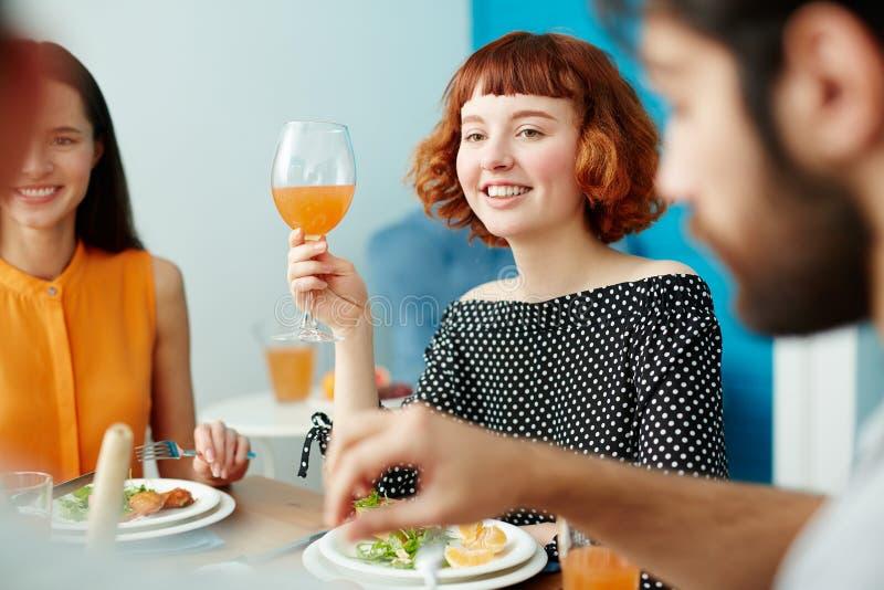 拿着玻璃的美丽的妇女,当吃与朋友时 免版税图库摄影