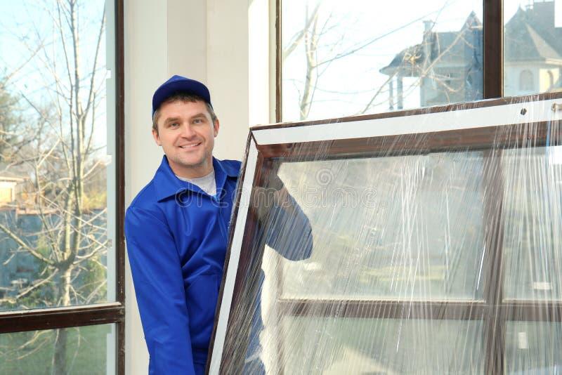 拿着玻璃窗的建筑工人 免版税库存照片