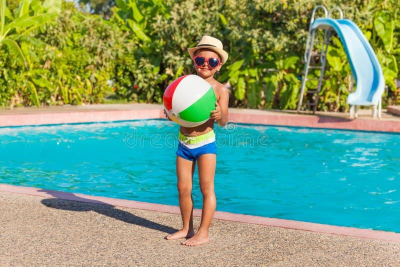 拿着球的帽子的男孩站立近的水池 免版税库存图片