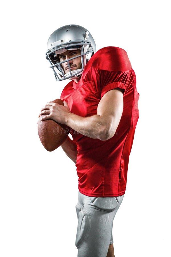 拿着球的红色球衣的严肃的美国橄榄球运动员 库存照片