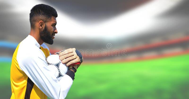 拿着球的足球运动员的综合图象在足球场内 库存照片