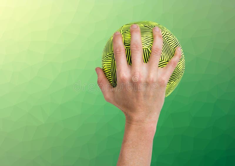 拿着球的运动员的手反对织地不很细绿色背景 库存图片