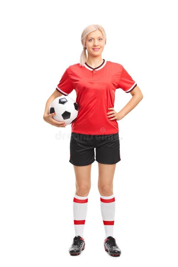 拿着球的年轻女性足球运动员 免版税图库摄影