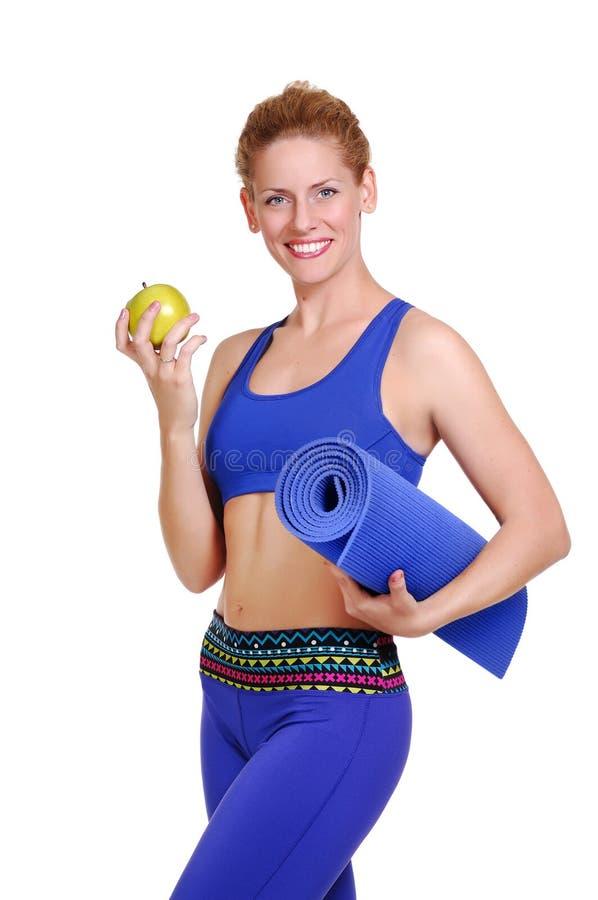 拿着瑜伽席子和一个新鲜的绿色苹果的嬉戏女孩 免版税图库摄影