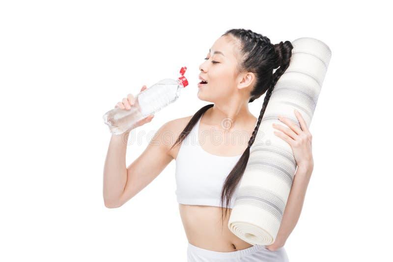 拿着瑜伽席子和饮用水从瓶的年轻亚裔妇女 免版税库存照片
