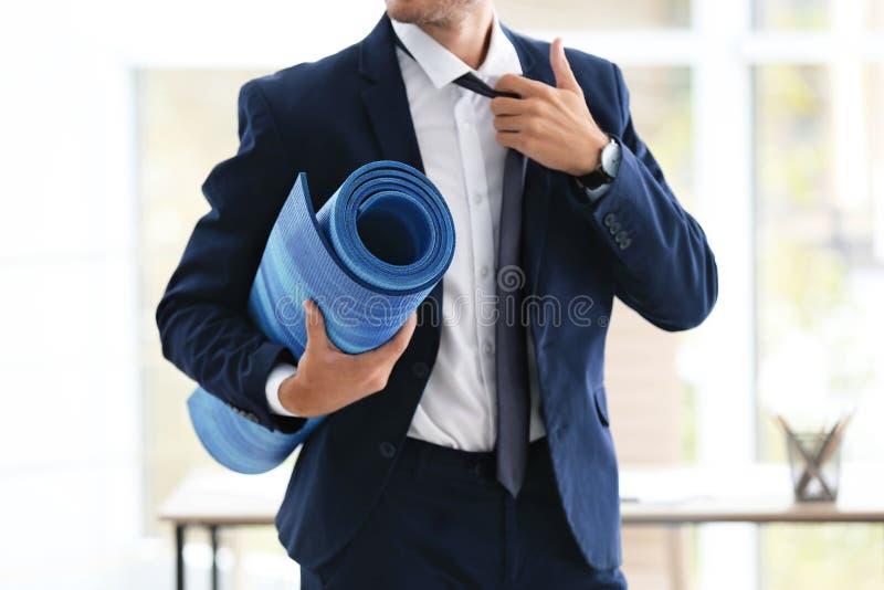拿着瑜伽席子的年轻英俊的商人在办公室 库存照片
