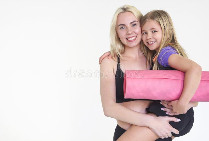 拿着瑜伽席子的母亲和女儿,隔绝在白色 免版税库存照片