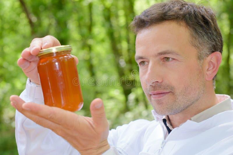 拿着瓶子蜂蜜的蜂农 库存图片