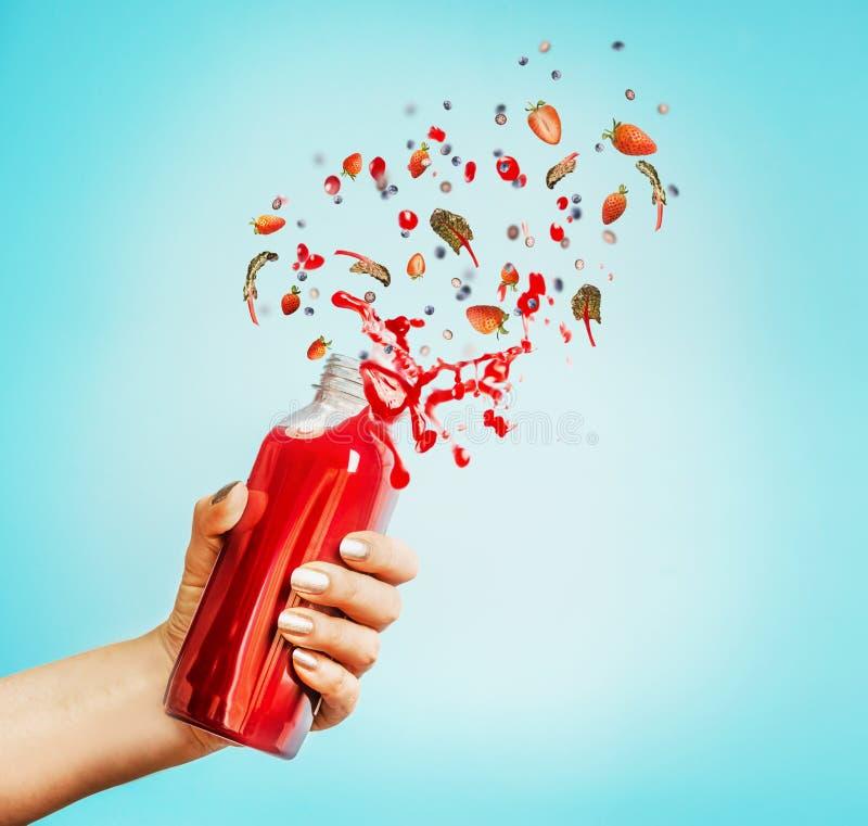 拿着瓶用红色飞溅夏天饮料的女性手:圆滑的人或汁液和莓果 图库摄影