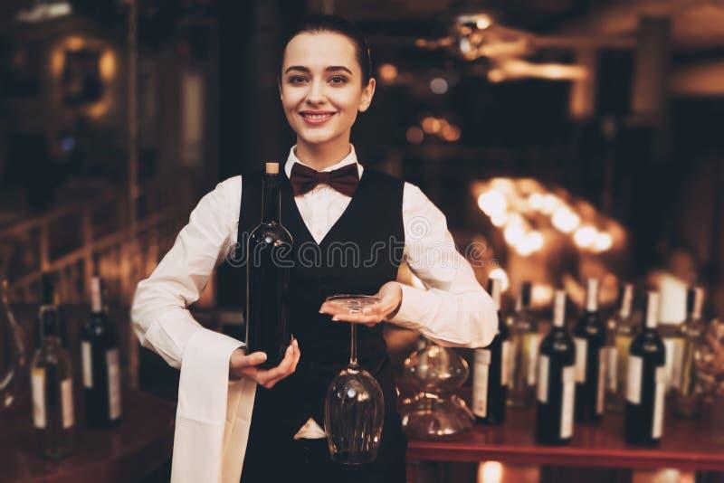 拿着瓶红葡萄酒和玻璃,站立的近的酒吧的快乐的典雅的女服务员 免版税库存图片