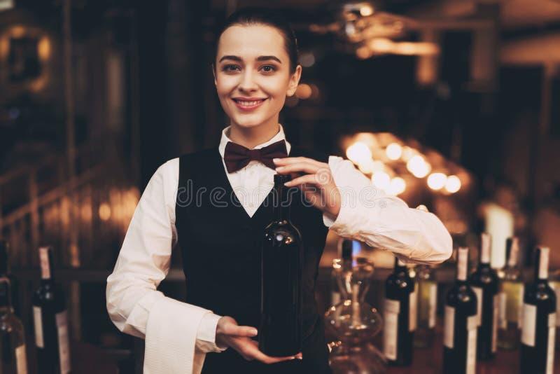 拿着瓶红葡萄酒,站立的近的酒吧的快乐的典雅的女服务员 免版税库存图片