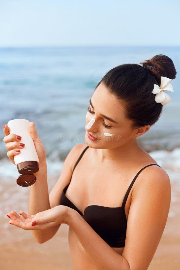 拿着瓶遮光剂的比基尼泳装的秀丽性感的年轻女人在她的手上 Skincare 一美丽的女性申请的防晒霜 Usin 库存照片